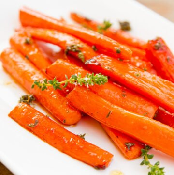 cooked carrots on a plate garnished with thyme