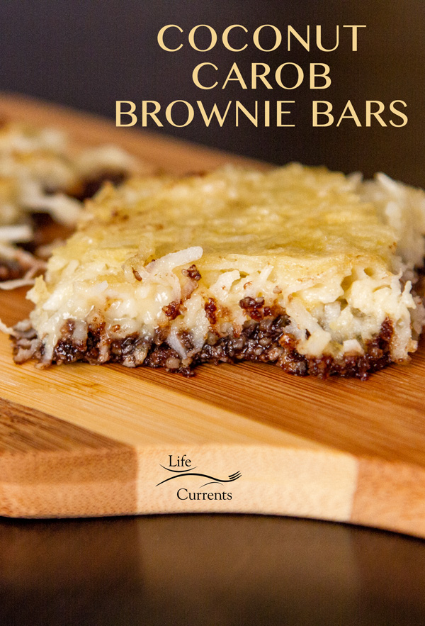 COCONUT CAROB BROWNIE BARS RECIPE on a wooden serving tray on a black background