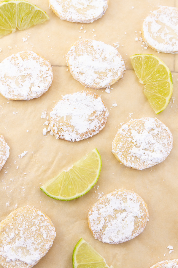 many cookies on a piece of parchment paper with slices of lime.