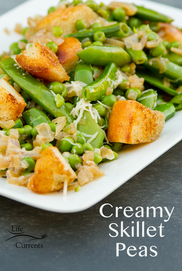 CREAMY SKILLET PEAS with croutons on a white platter on a grey background with a title