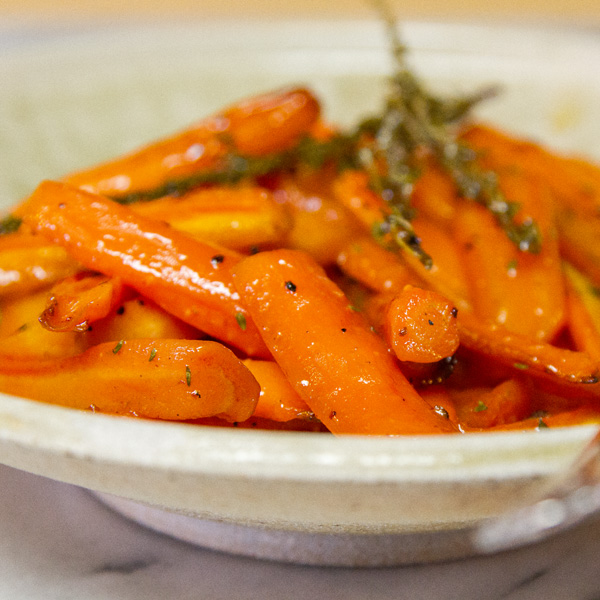 close up on roasted cooked carrots on a serving plate