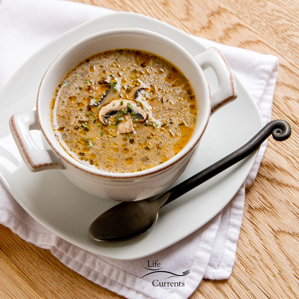 mushroom soup in a bowl with handles, a spoon on the lower right. All on a white plate on a white napkin on wood background