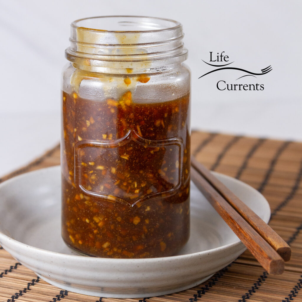 square crop of teriyaki sauce in a jar on a plate with chopsticks next to it.
