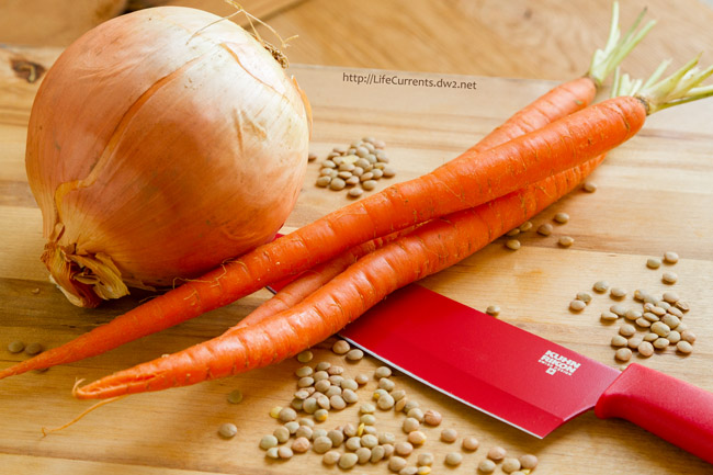 an onion, carrots, lentils and a knife on a cutting board