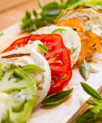 Plank Grilled Blue Cheese Caprese is a fun way to enjoy Caprese as an appetizer or a salad. The combination of sweet tomatoes, savory melted blue cheese, and smoky grilled onions is simply divine!