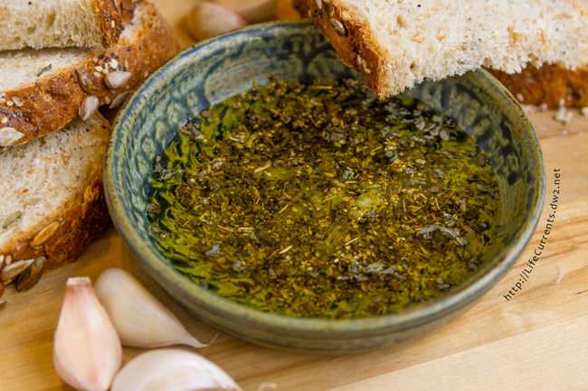 bread dipping oil in a bowl with slices of bread and cloves of garlic