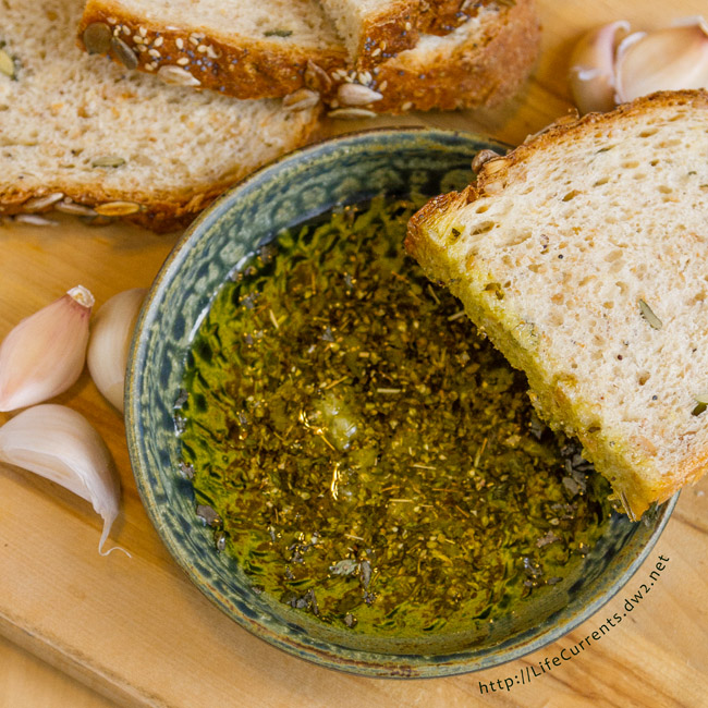 square crop of herb oil in a bowl with slices of bread