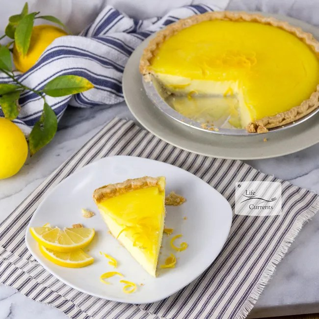 Grandma's Lemon Custard Pie a slice of pie garnished with lemon slices served next to the whole pie and some whole lemons
