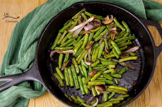 Easy Roasted Green Beans with Mushrooms and Onions in a cast iron skillet with a green towel
