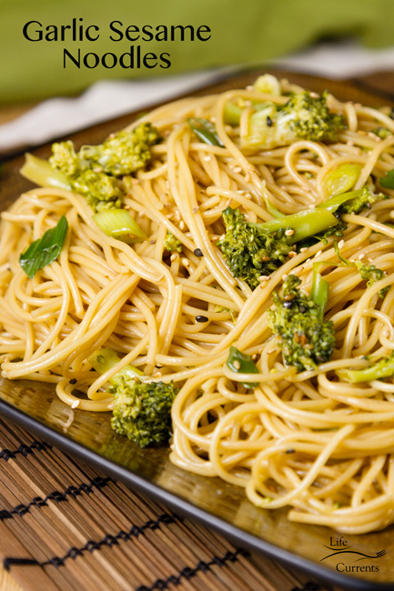 Garlic Sesame Noodles - Asian noodles with broccoli on a brown square plate with a green napkin in the background