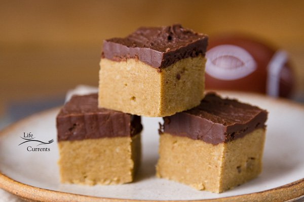 peanut butter and chocolate bars stacked on a plate with a football in the background.