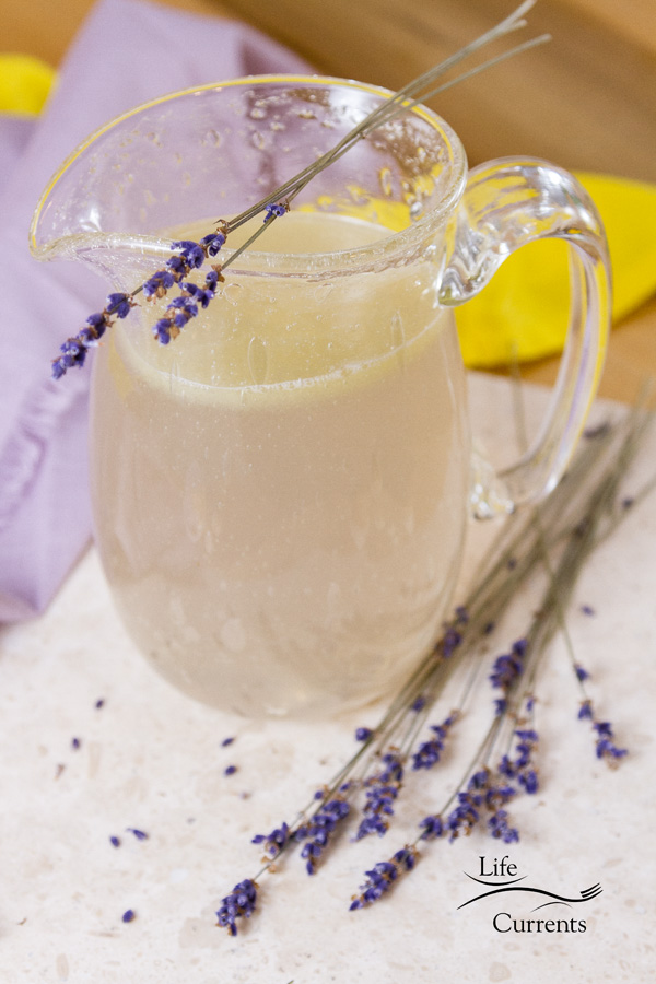 Pretty Pink lemonade in a glass pitcher with lavender sprigs