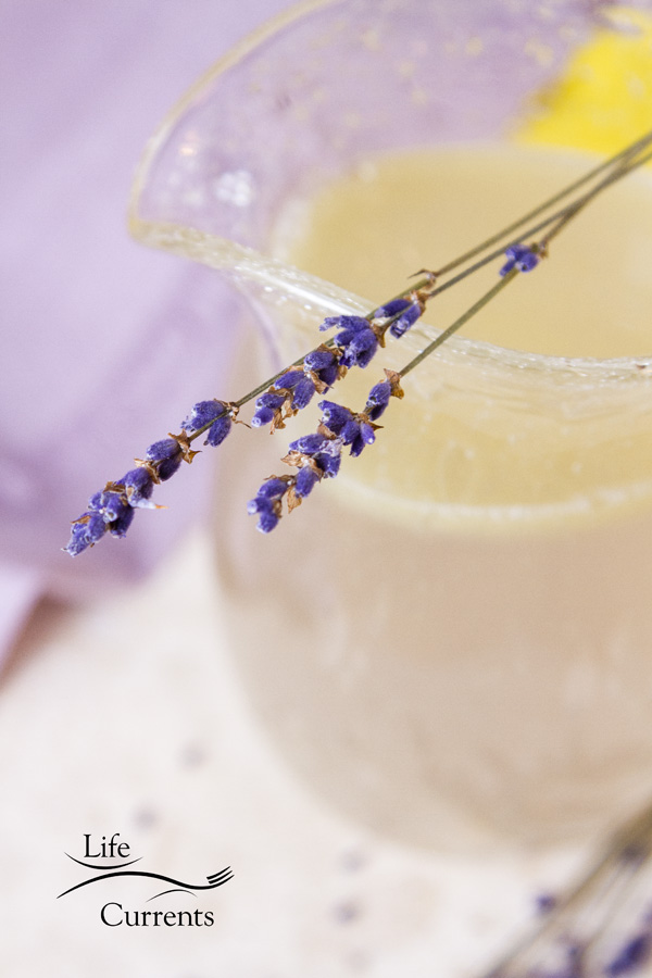 Purple lavender sprigs on top of a glass picher filled with lavender lemonade