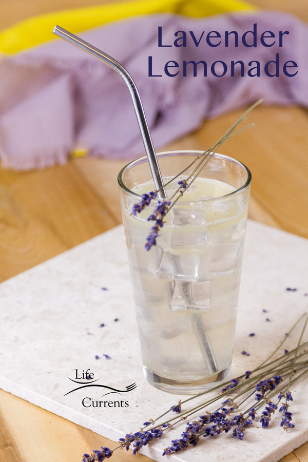 Lavender Lemonade in a glass with ice and a reusable stainless steel straw