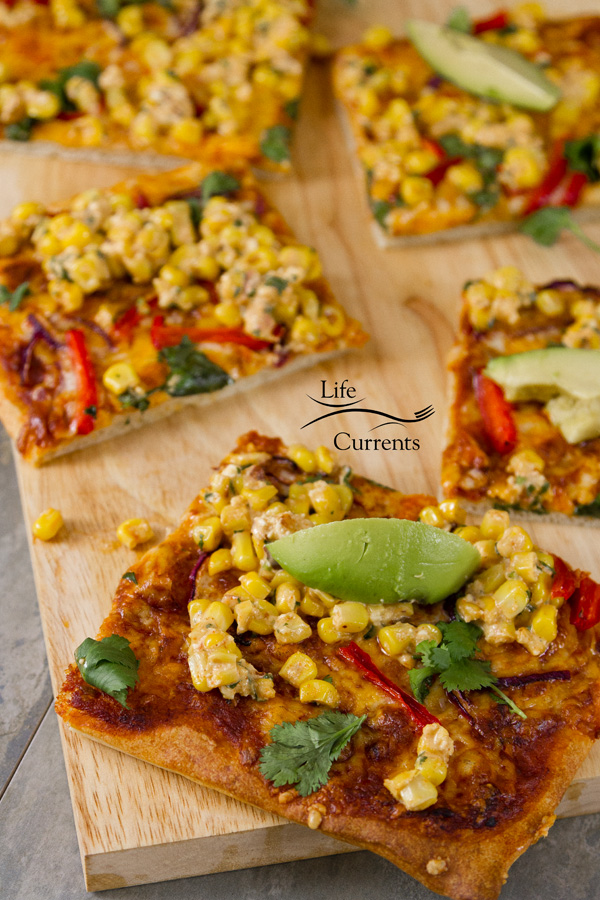 Mexican Street Corn Pizza on a wooden cutting board, topped with avocado, red peppers, cilantro