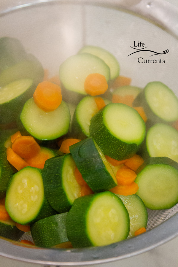 Zucchini and carrots lightly boiled and draining in a strainer with steam coming off of them