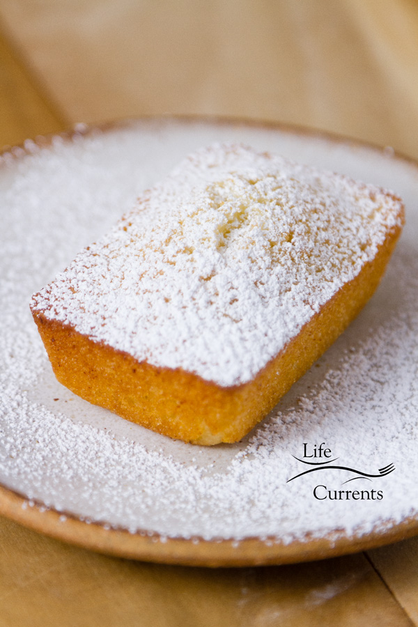 Financiers (French Almond Cakes) dusted with powdered sugar on a white plate
