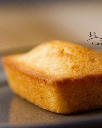 square image of the financier cake, a simple almond cake on a gray plate
