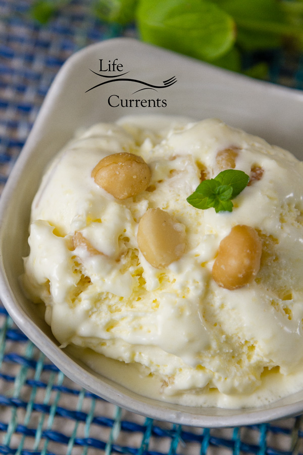 Pineapple Macadamia Nut Ice Cream in a white bowl garnished with macadamia nuts and a sprig of mint on blue fabric