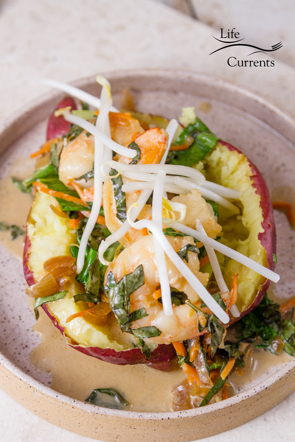 cooked shrimp and veggies stuffed in a sweet potato topped with bean sprouts on a white plate on a white background