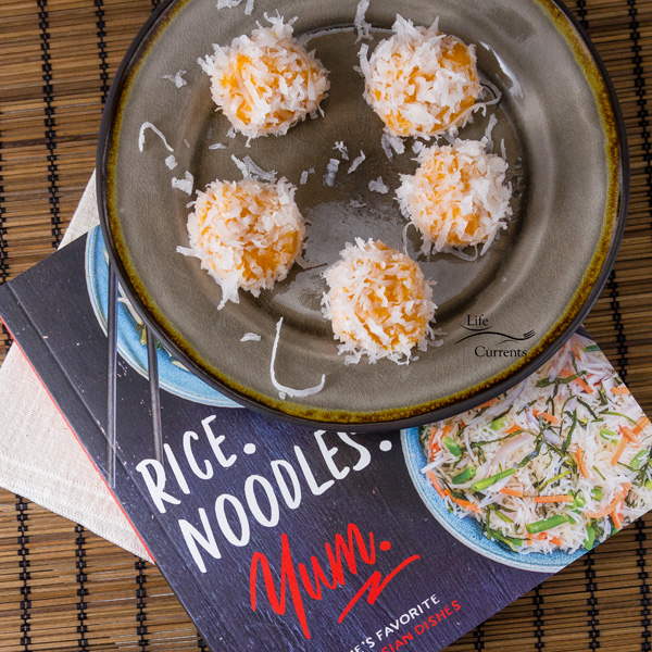 Sweet Potato Rice Balls or Ondeh Ondeh on a grey plate on top of the cookbook Rice. Noodles. Yum.