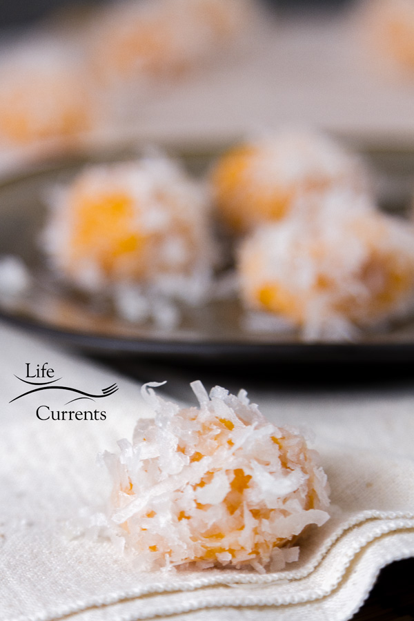a sweet potato rice ball in the front of the picture on a white napkin with a gray plate full of more rice balls