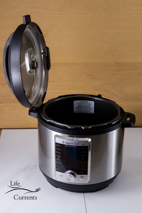 The Instant Pot with the lid resting in the side slot or handle