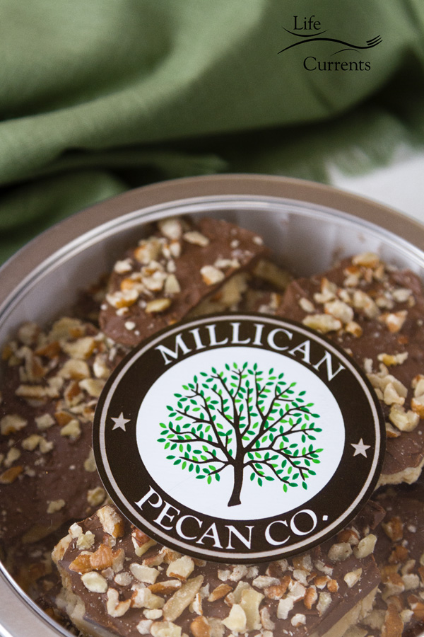 Millican Pecan Dark Chocolate Pecan Toffee Tin with a green napkin in the background
