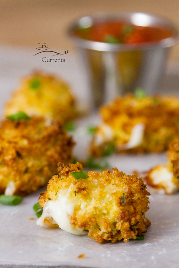 serveral breaded mozzarella bites with cheese oozing out garnished with green onions and served with marinara sauce