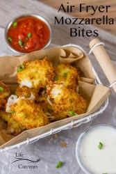 mozzarella pieces coated in bread crumbs air fried in a wire basket with a brown paper liner served with small aluminium ramekins of marinara sauce and ranch dressing garnished with green onions
