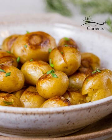 cooked potatoes in a white ceramic bowl on a brown platter with rosemary in the background