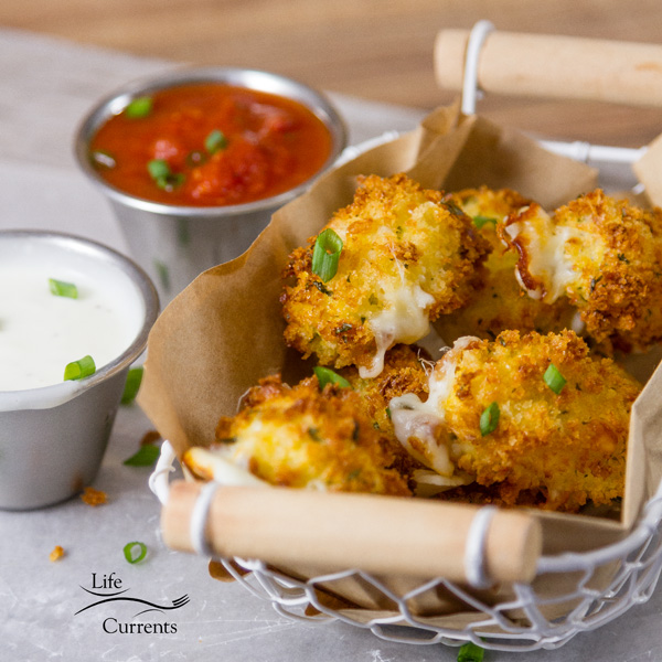Air fryer mozzarella bites served in a wire basket with wooden handles along with ranch and marinara for dipping