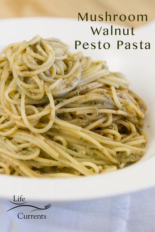 Spaghetti noodles with mushroom basil walnut pesto served in a white bowl