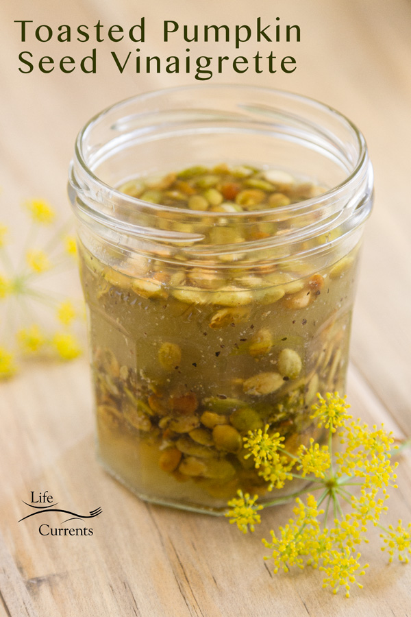Toasted Pumpkin Seed Vinaigrette in a small glass jar with yellow flawers next to it all on a wood background
