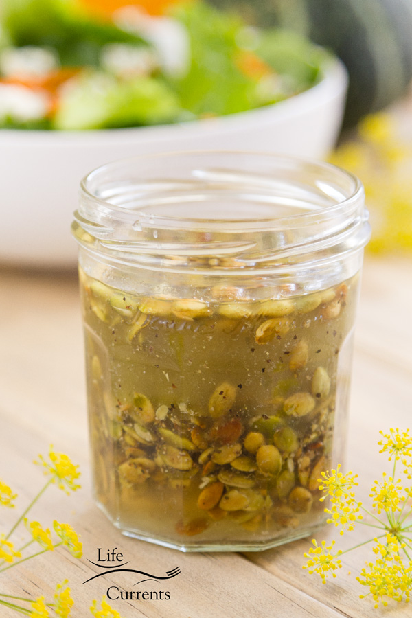 Toasted Pumpkin Seed Vinaigrette in a glass jar with a green salad