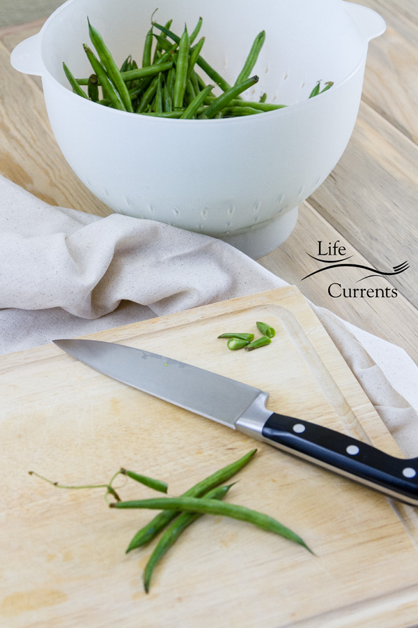 cleaning green beans, a knife to cut the ends off and the cleaned green beans in a colander