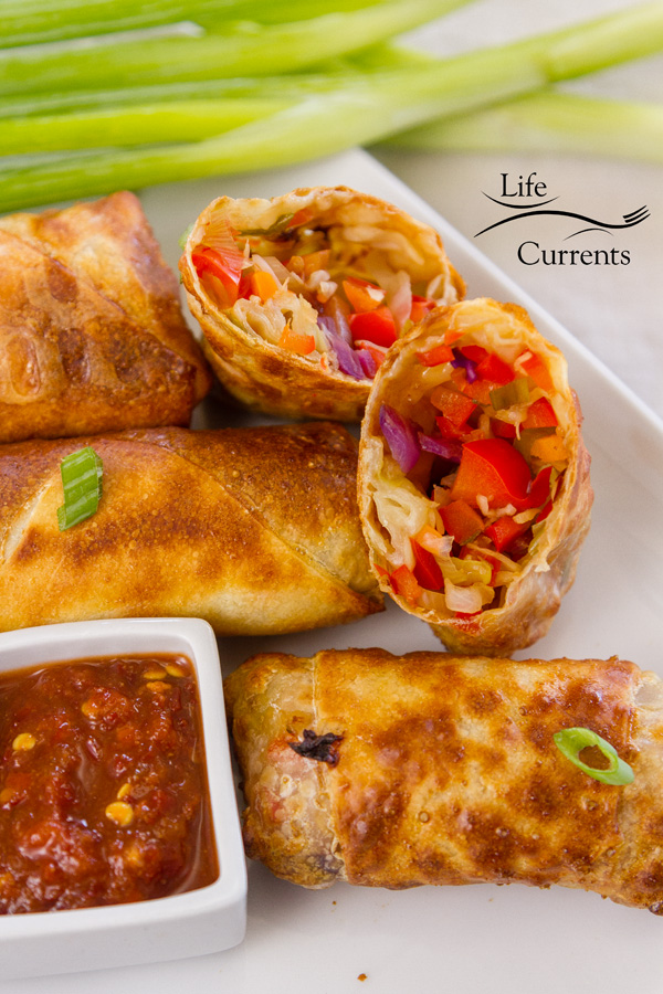Egg rolls, one cut open, with green onions on the side and some chili garlic paste