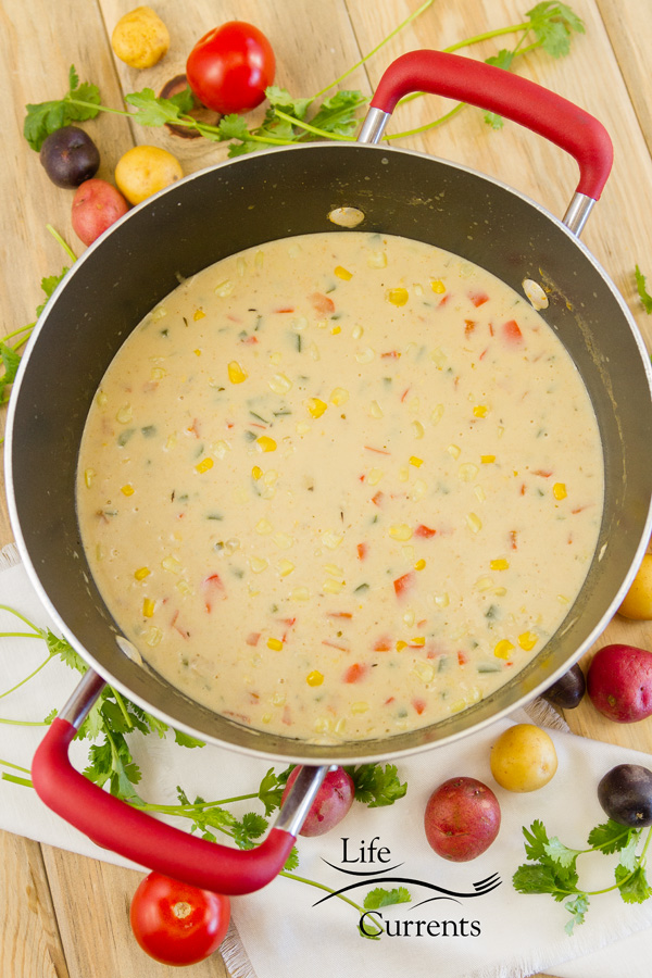 Southwestern Corn Chowder in a pot with red handles surrounded by veggies on a wooden background