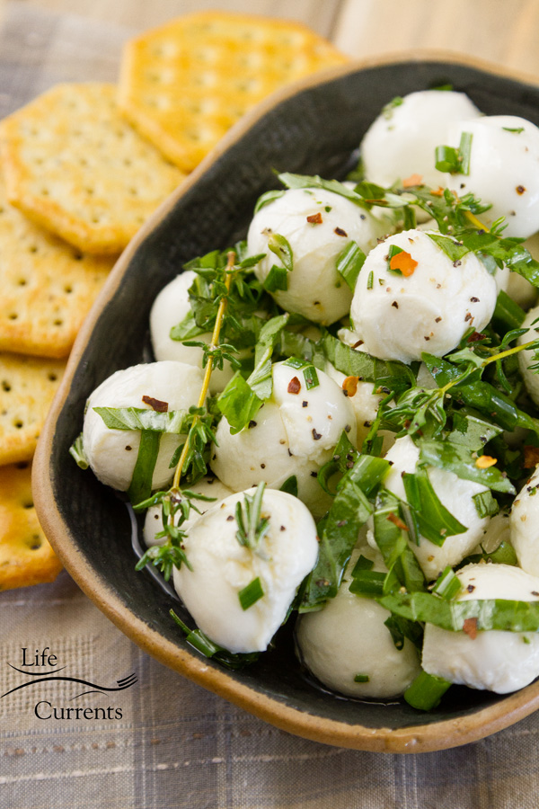 marinated mozzarella in a dark bowl with crackers