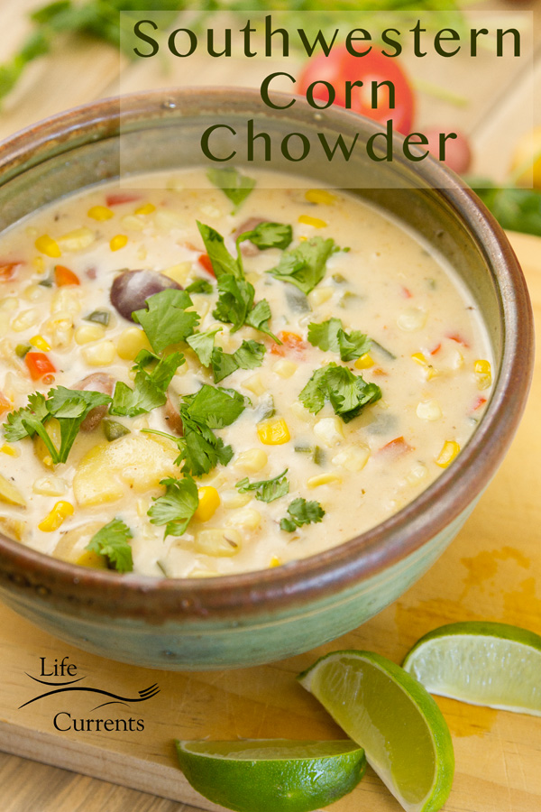 Corn chowder in a ceramic bowl with cilantro garnish and lime wedges surrounded by different veggies