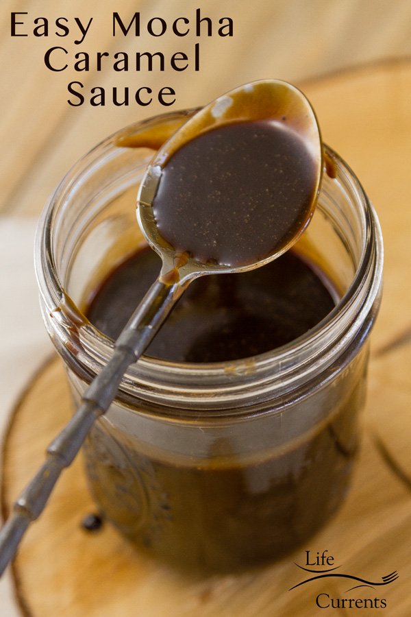 Easy Mocha Caramel Sauce in a mason jar with as spoon on top of the jar and sauce in the bowl of the spoon