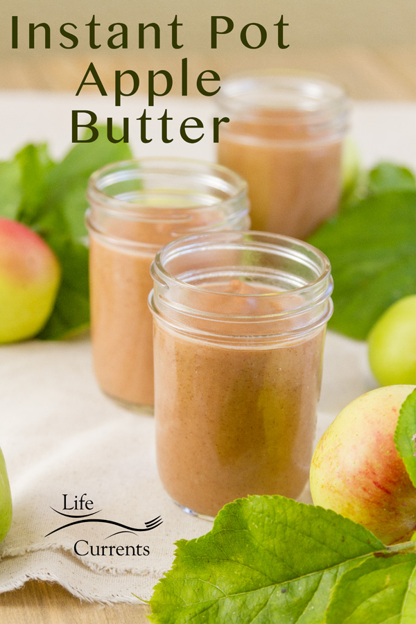 3 mason jars with apple butter inside some green and red apples and apple leaves around