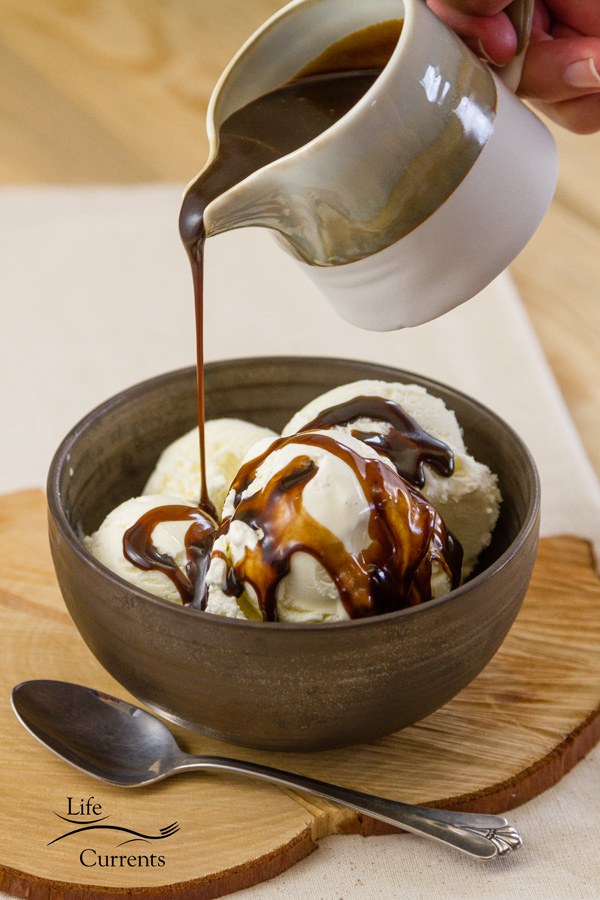 Mocha Caramel Sauce being poured over vanilla ice cream with a spoon in a dark bowl on a piece of wood