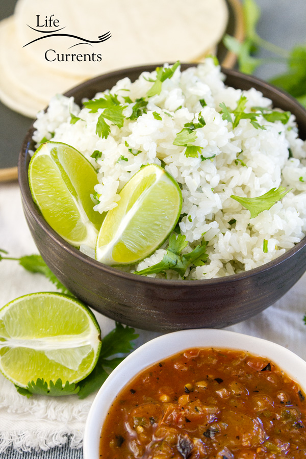 a bowl of cilantro lime rice in a dark brown bowl served with salsa and tortillas on the side