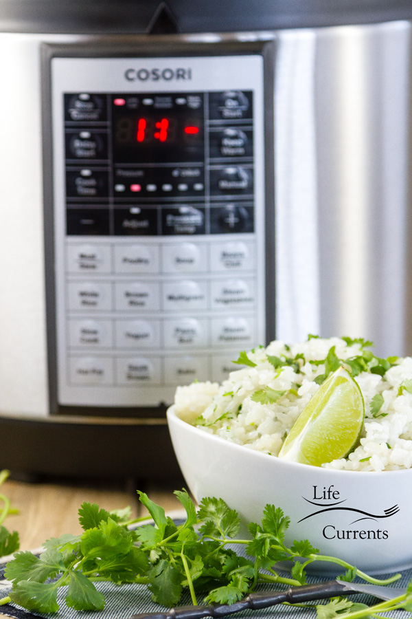 a bowl of cilantro lime rice with cilantro and lime wedges set in front of a COSORI pressure cooker