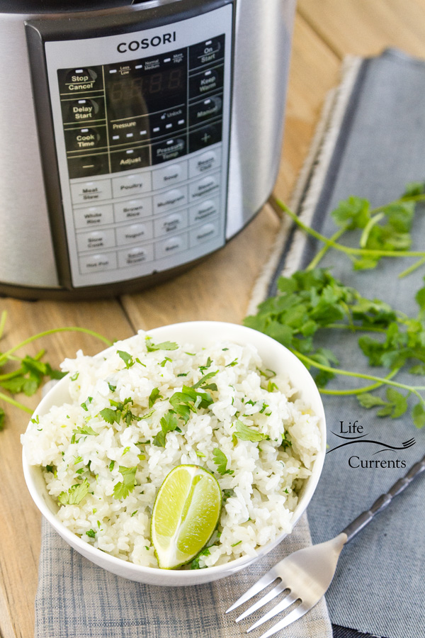 a pressure cooker with a bow of rice some cilantro stems, a fork, and 2 cloth napkins