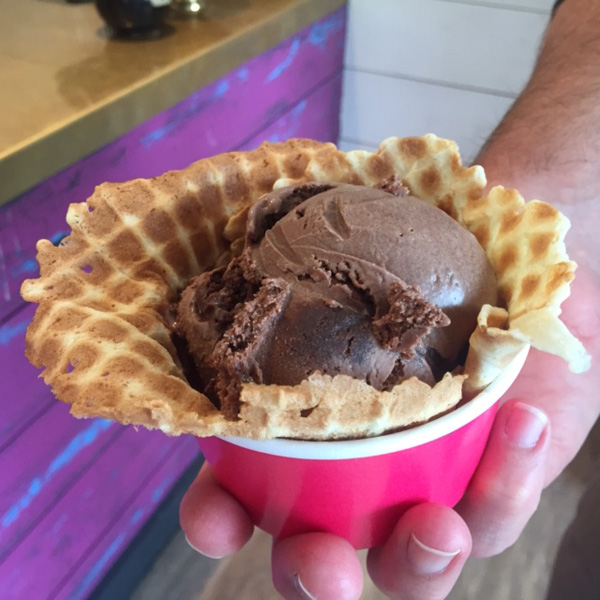 chocolate ice cream in a waffle cone in a pink cup