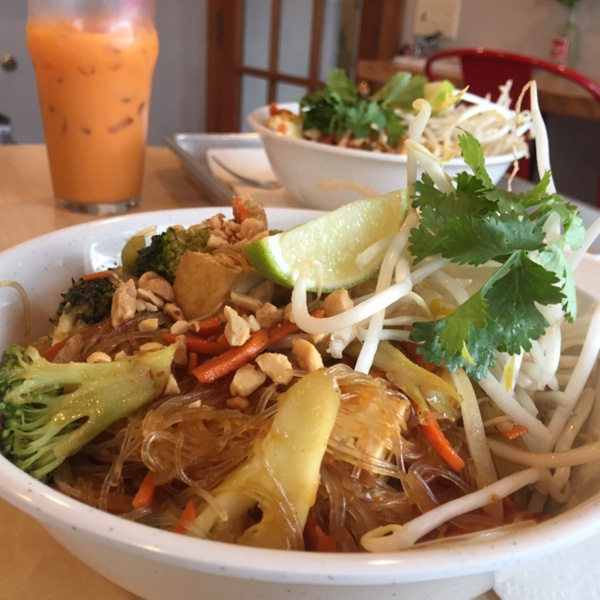 Tow bowls of Pad Thai with a Thai Ice Tea in the background