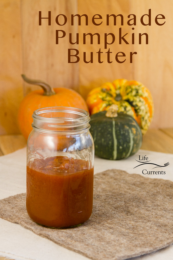 a jar of pumpkin butter in front of some squash on a brown felt pad