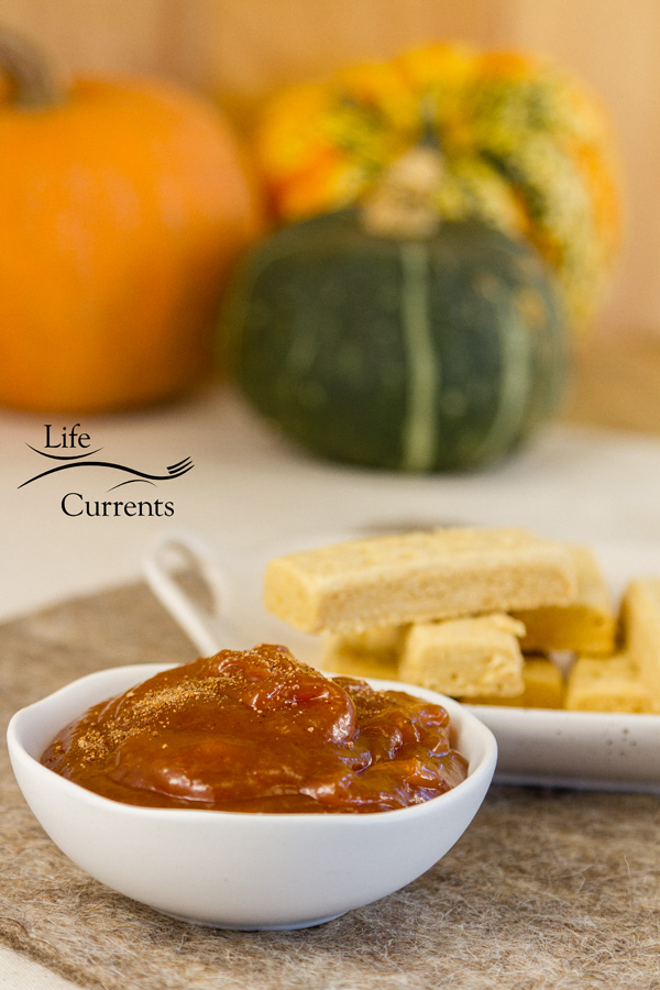 pumpkin butter in a dish with shortbread cookies and some pumpkins in the background